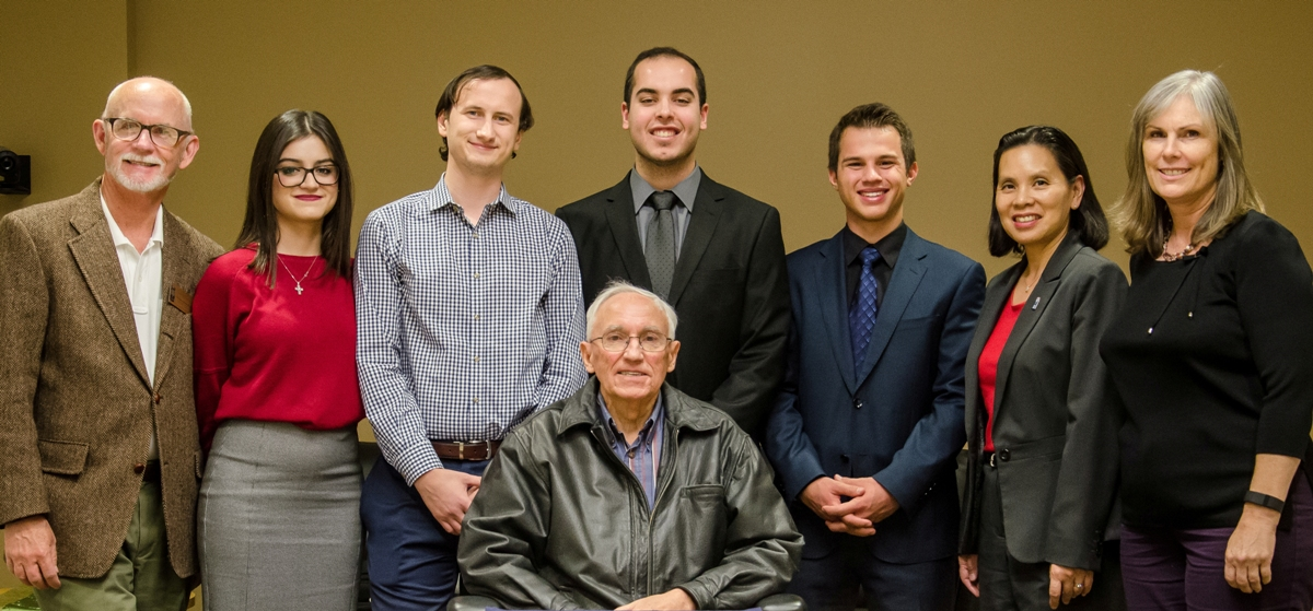Mihaylo College finance faculty and students stand while accounting alumnus Paul Folino sits at a Nov. 2015 event.