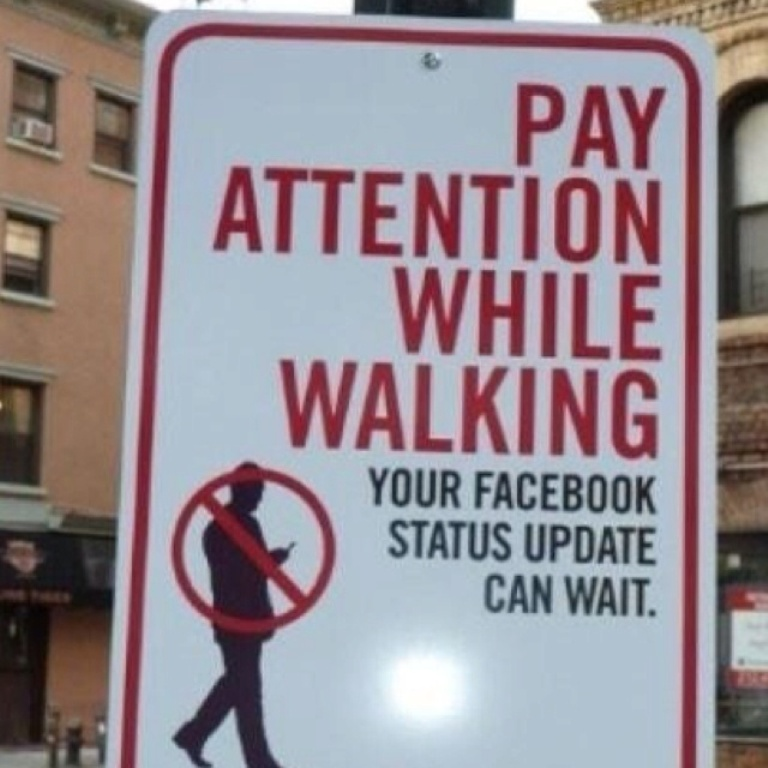 Pedestrians are urged to get off their smartphones in this street sign, emblematic of our tech-obsessed culture.