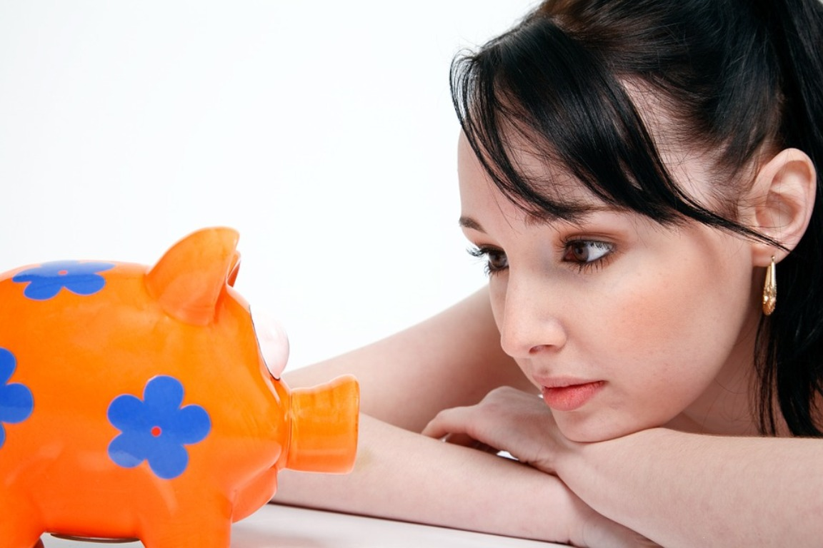 A young woman ponders her financial future as she looks at a plastic piggybank.