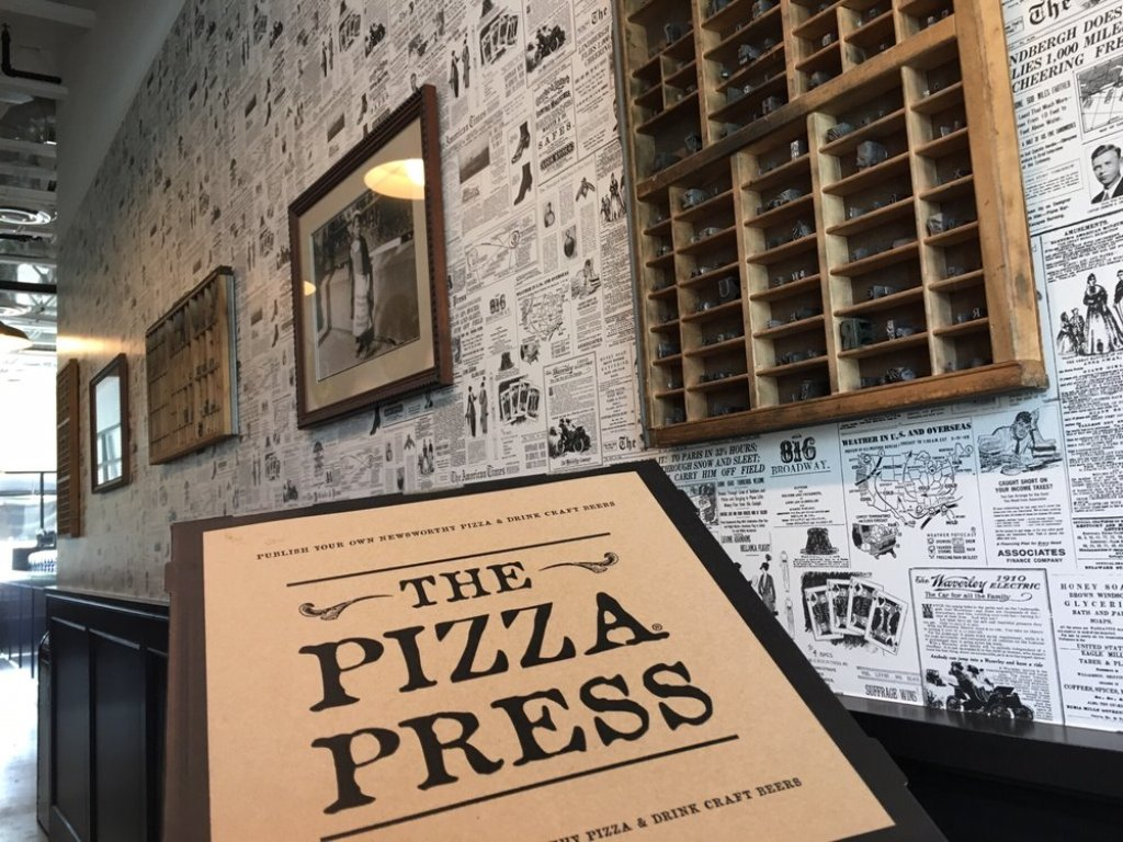 The interior of the Pizza Press on Nutwood Avenue in Fullerton, which features retro newspapers as wallpaper and an overall journalistic theme.