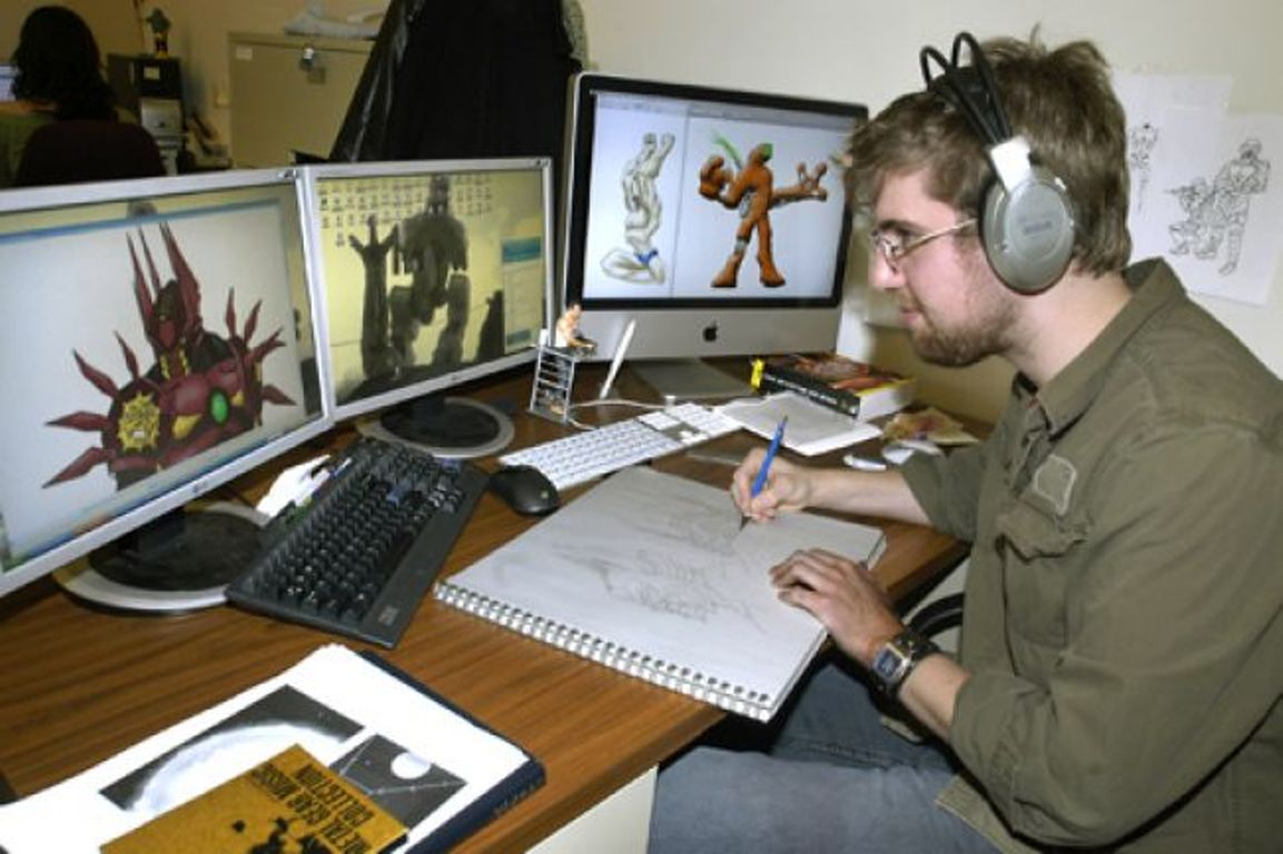 A graphic artist sits at a desk with three computer monitors open as he designs a video game.