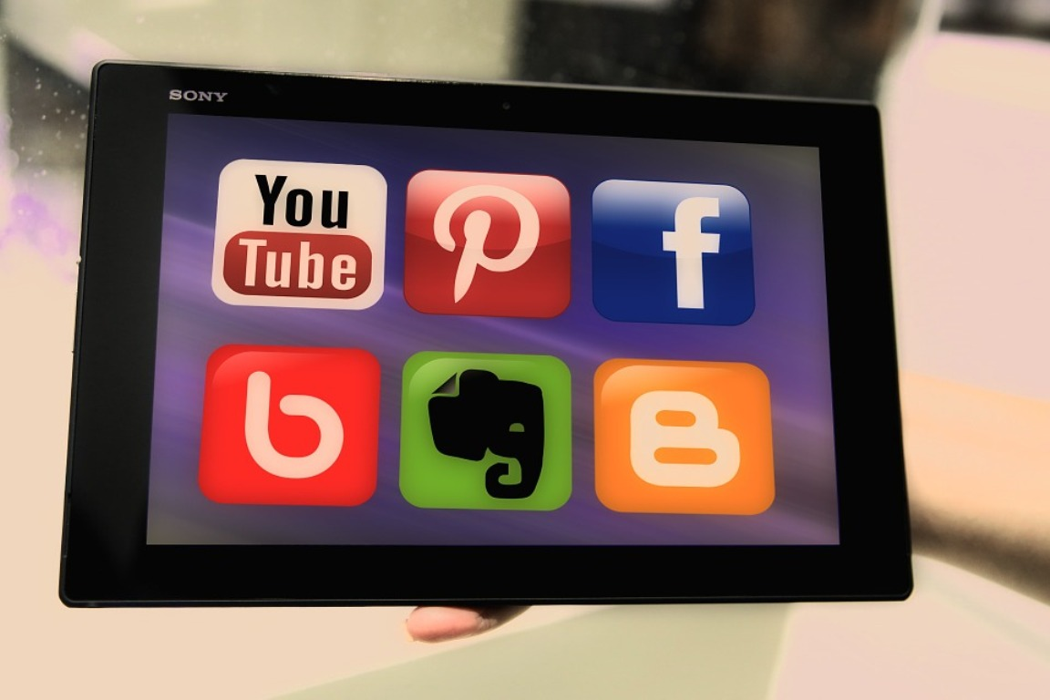 A person holds an iPad with the logos of major social networking sites.