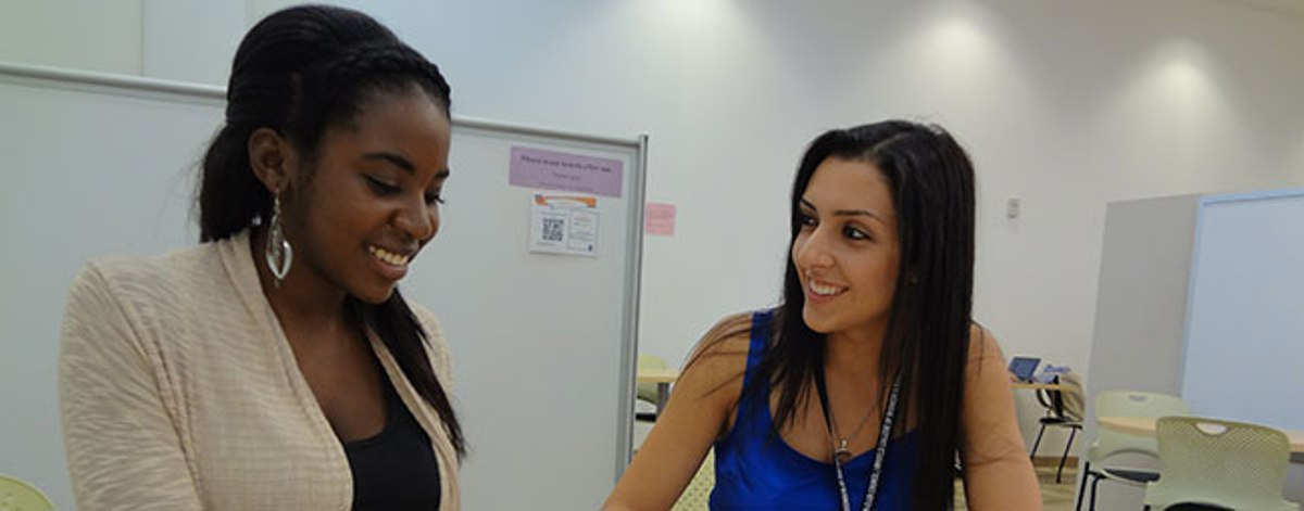 Two young women talk at the Mihaylo College Tutoring Center, which provides peer advising for Cal State Fullerton business students facing difficult coursework.