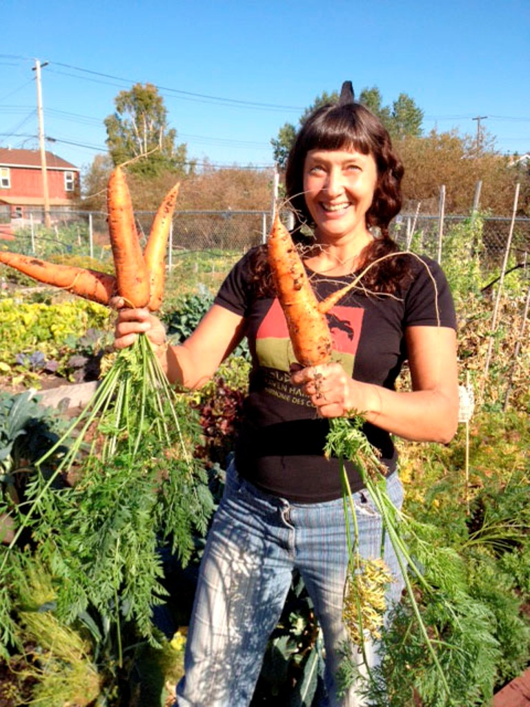 Loren Sorensen holds large carrots harvested in Yellowknife, Northwest Territories, Canada, which is above the Arctic Circle.