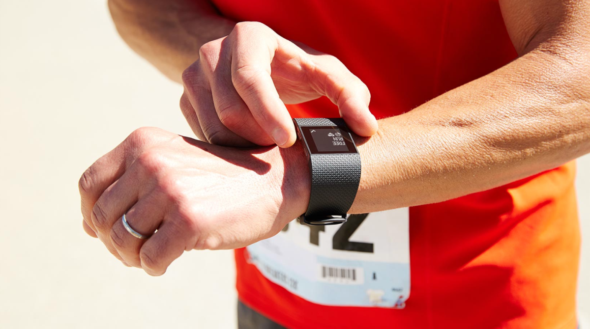 A person in athletic attire monitors a wristband fitness tracking device.