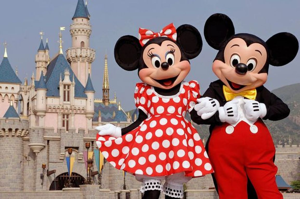 Minnie and Mickey Mouse stand outside Sleeping Beauty Castle at Disneyland.