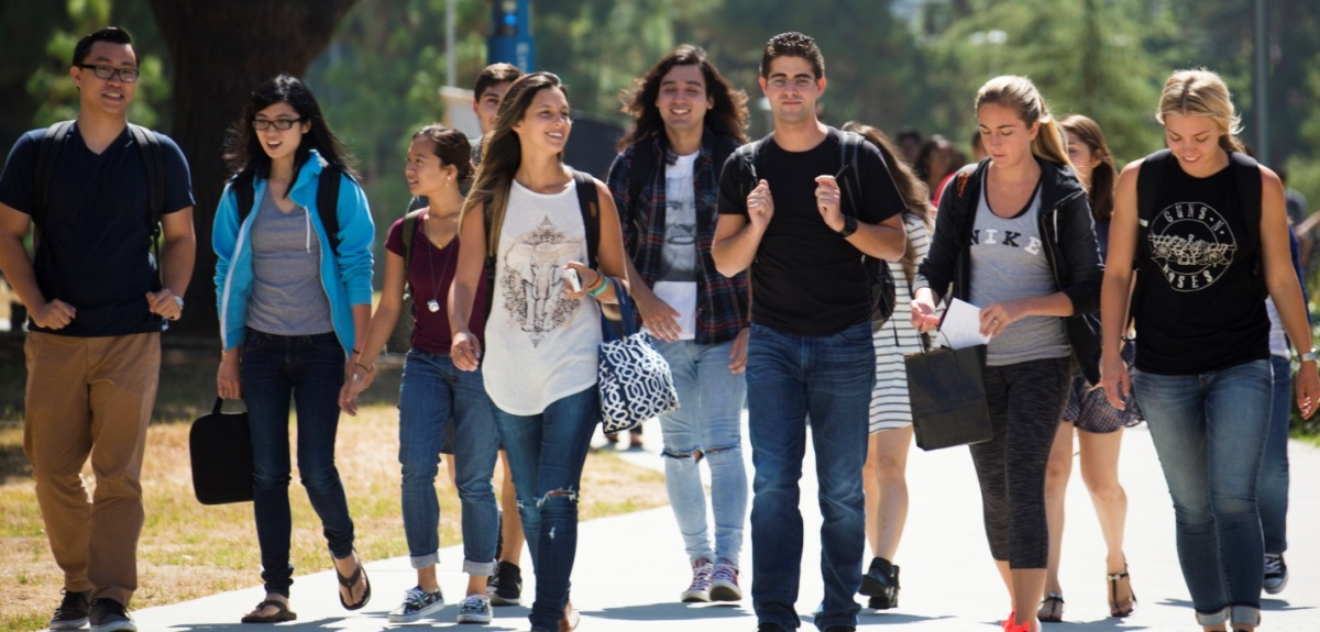 A diverse group of Cal State Fullerton students walking across campus on a sunny day.