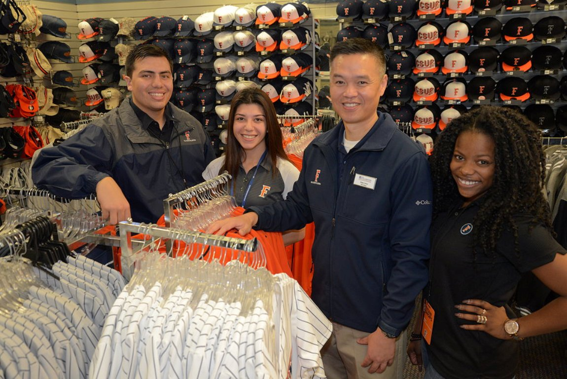 A diverse group of student employees at Cal State Fullerton's Titan Shops pose amidst the Titan-themed clothing on sale at the store.
