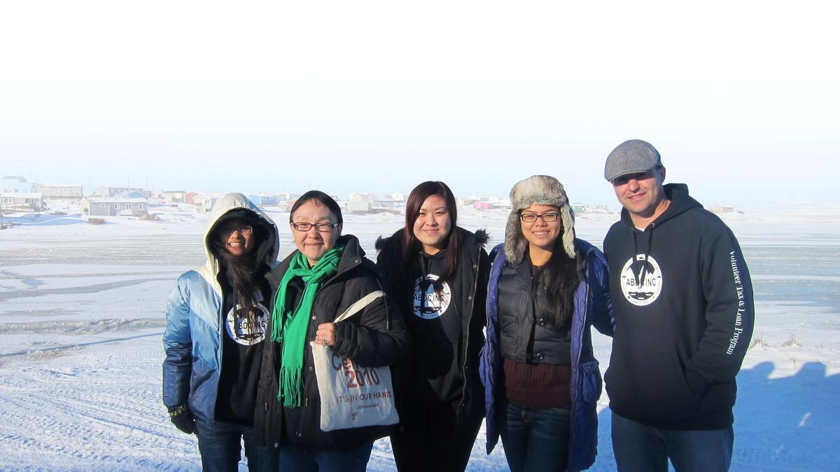 A group of four Mihaylo College students and a village contact posing in the barren Arctic of Alaska.