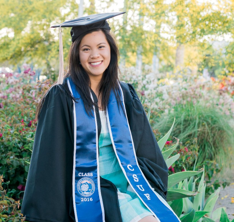 Lydia Wang, a 2016 Mihaylo College grad and commencement speaker, at the Fullerton Arboretum in cap and gown.