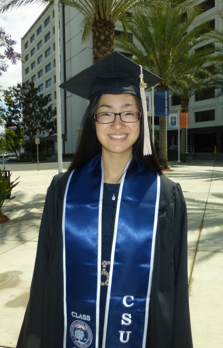Amanda Tran, a 2016 Mihaylo College grad, stands in cap and gown outside of College Park at Cal State Fullerton.