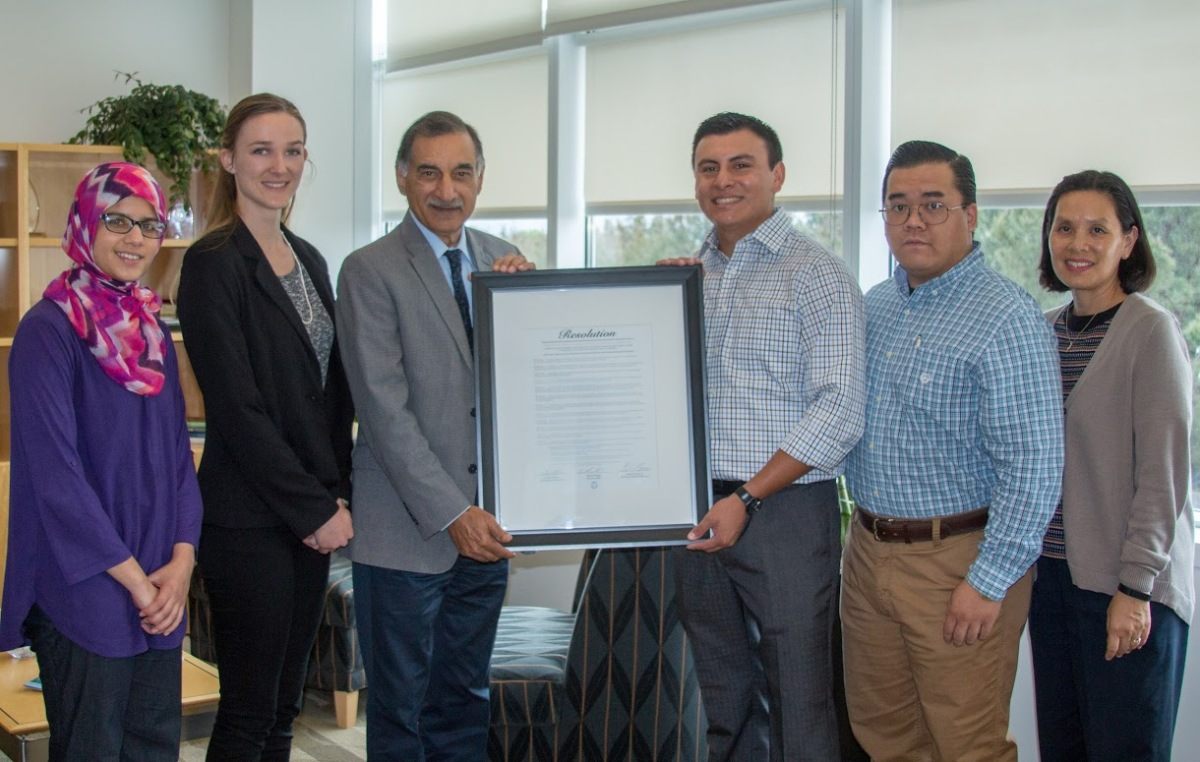 Mihaylo College Dean Anil Puri is presented a framed copy of a Cal State Fullerton Associated Students Inc. honorary resolution.