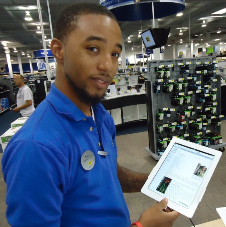 A Best Buy sales associate holds an iPad on the sales floor of a busy store.