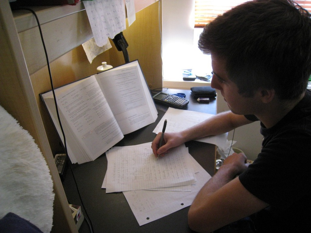 A male college student studying for final exams in his dorm room.