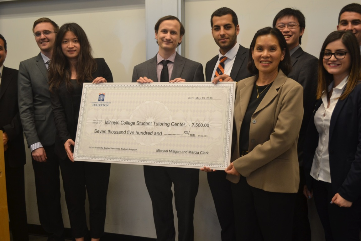 Mihaylo College students enrolled in the applied investment program present a giant check to Assistant Dean for Student Affairs Emeline Yong.