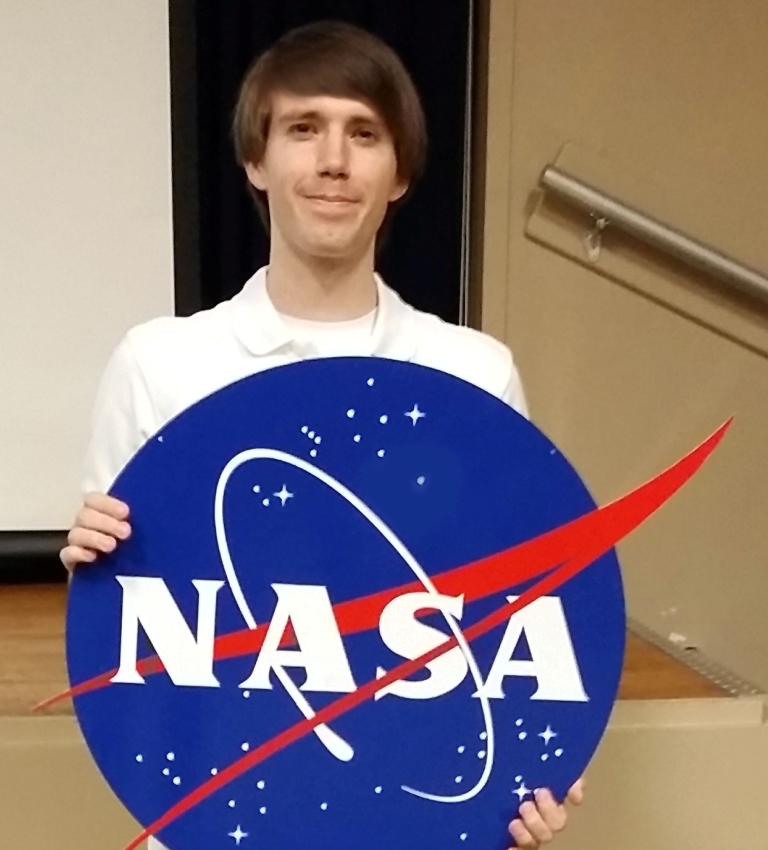 Christopher Stewart '15, a Mihaylo College international business grad, poses with the NASA logo at the Johnson Space Center in Houston, Texas, where he interned in 2016.