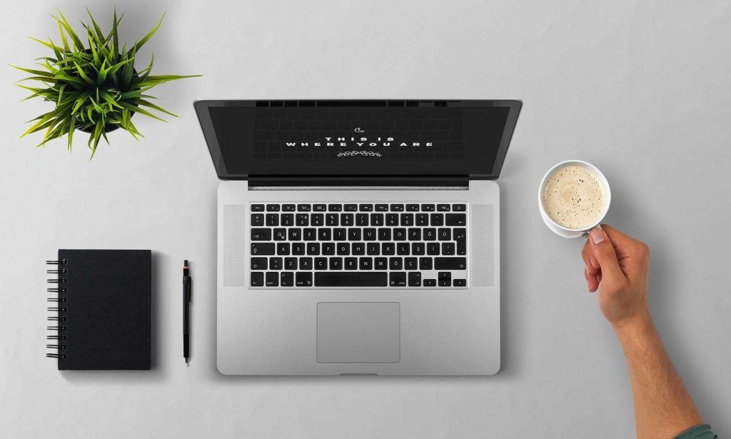 A person sets a cup of coffee next to a laptop computer, journal and pen, and potted plant.