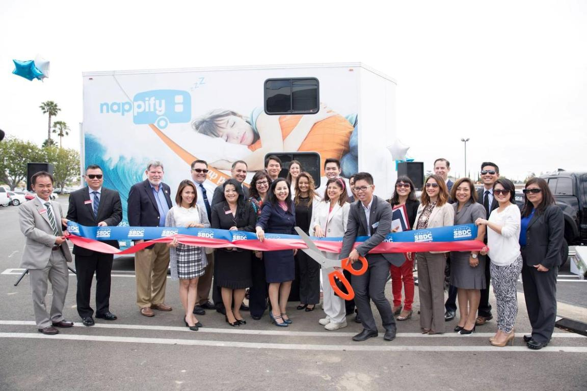 Kevin Pham, founder of Nappify, cuts the ribbon in front of his mobile nap pod, while officials from Lead SBDC and local business professionals look on.