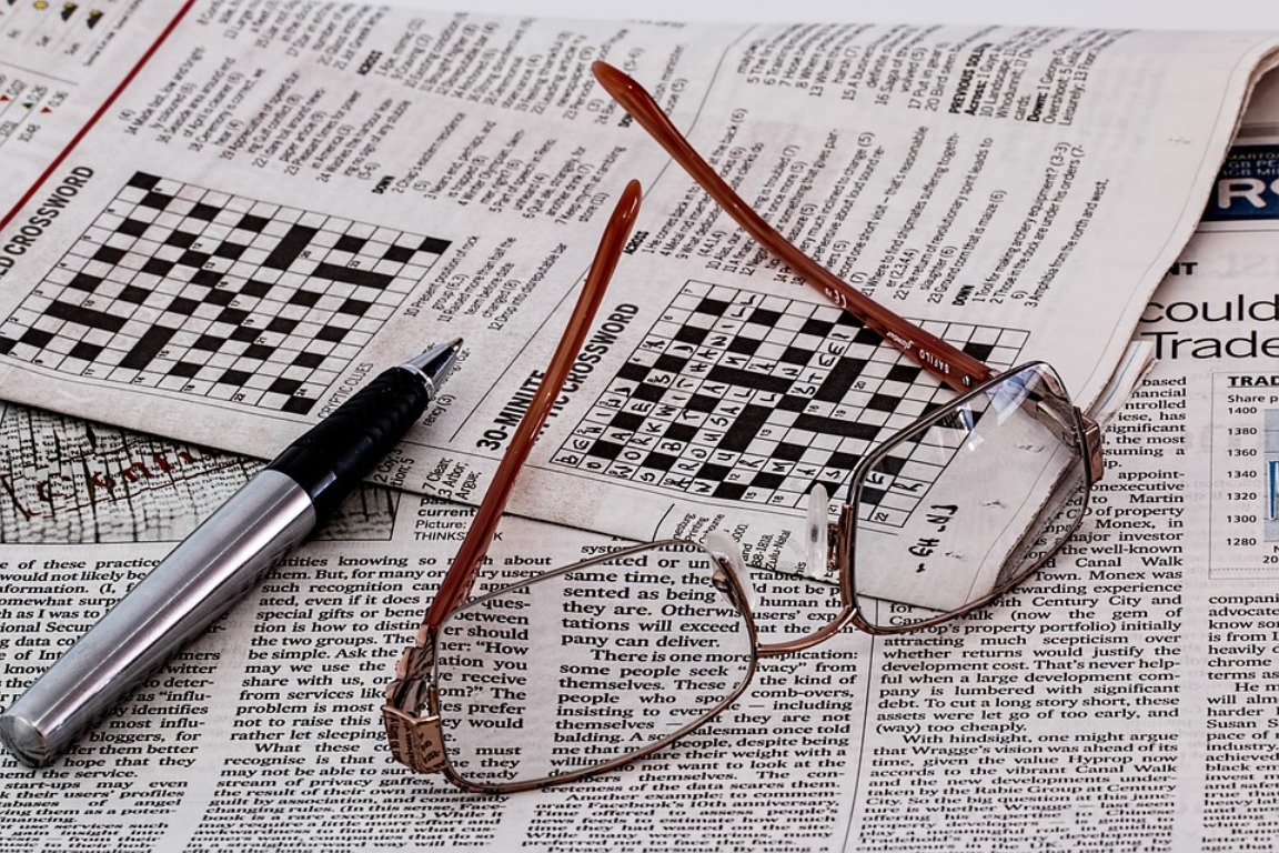 Eyeglasses set atop newspapers and crossword puzzles.