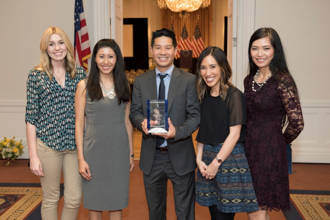 Mihaylo College alumnus Tam Nguyen '05 holds an award his business was given at the Center for Family Business Hall of Fame awards. He is surrounded by his executive team