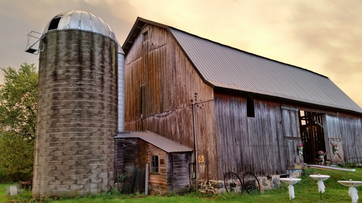 An abandoned barn and silo against a stormy sky in the American Midwest.