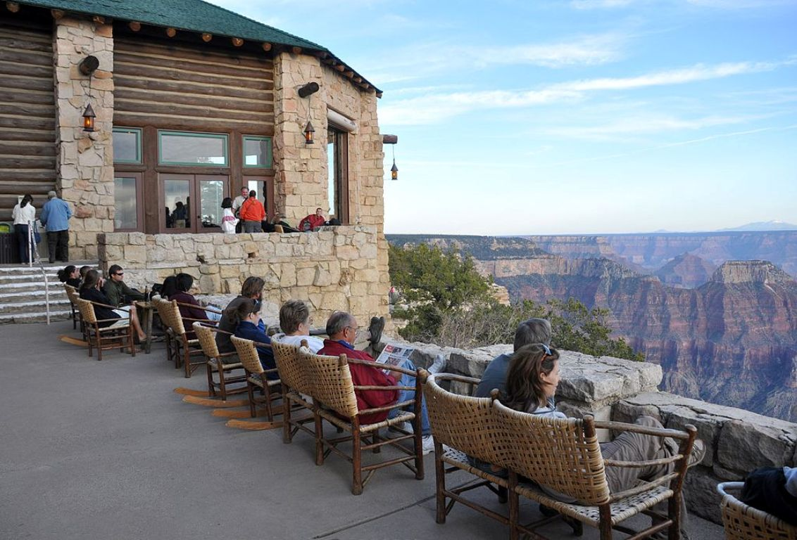 Visitors look down into the chasm of the Grand Canyon from an observation point.