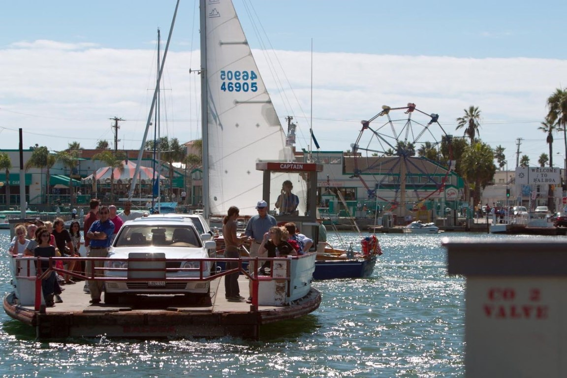 The Balboa Island Ferry departs at Newport Beach, California, filled with vacationers.