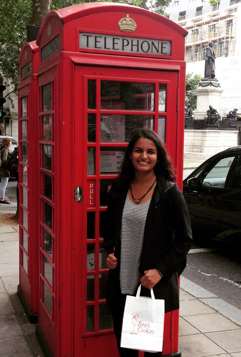 Mihaylo marketing and ISDS student Elisha Gupta poses next to a red telephone booth on the streets of London, England.