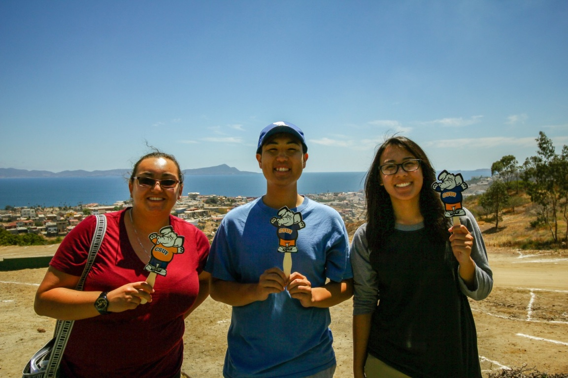 Three Mihaylo College students hold handheld Tuffy icons, with the Ensenada, Mexico, harbor in the background.