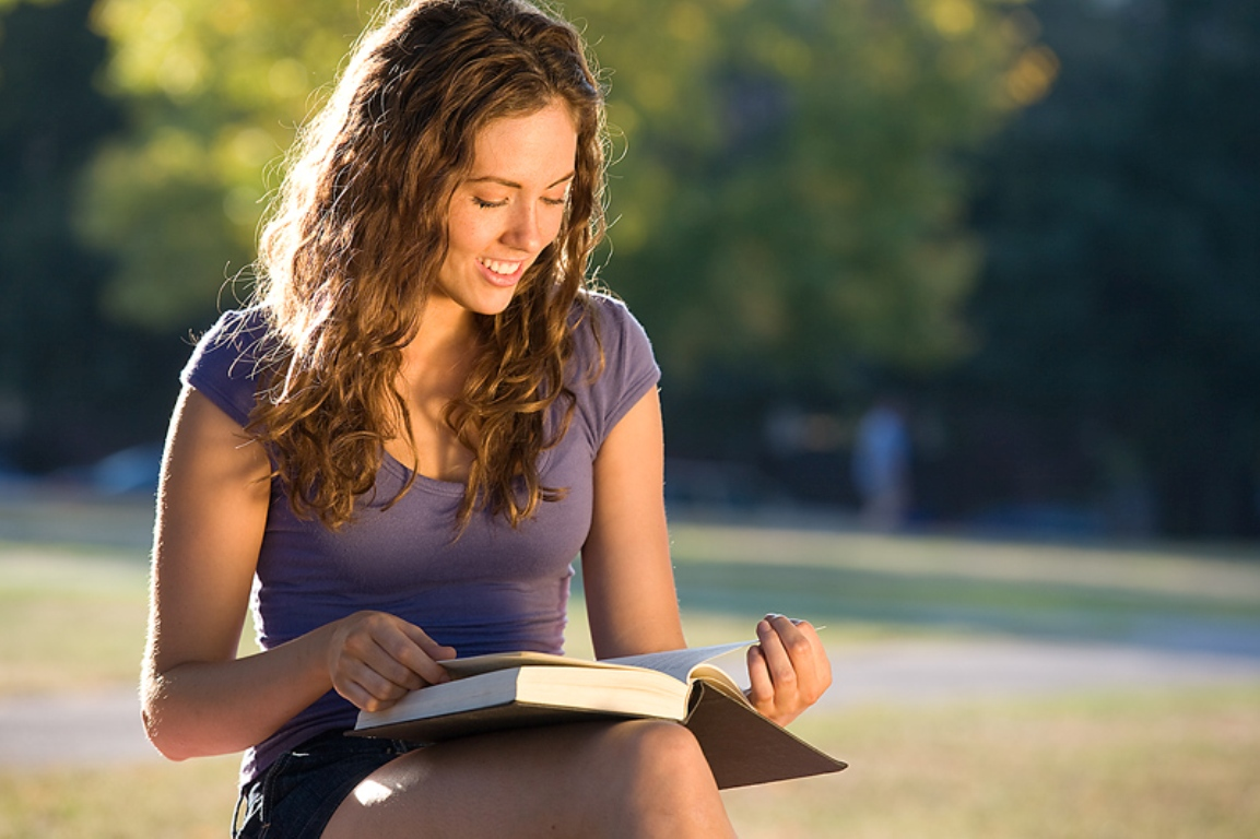 A light brunette young woman reads a book amidst a park setting.