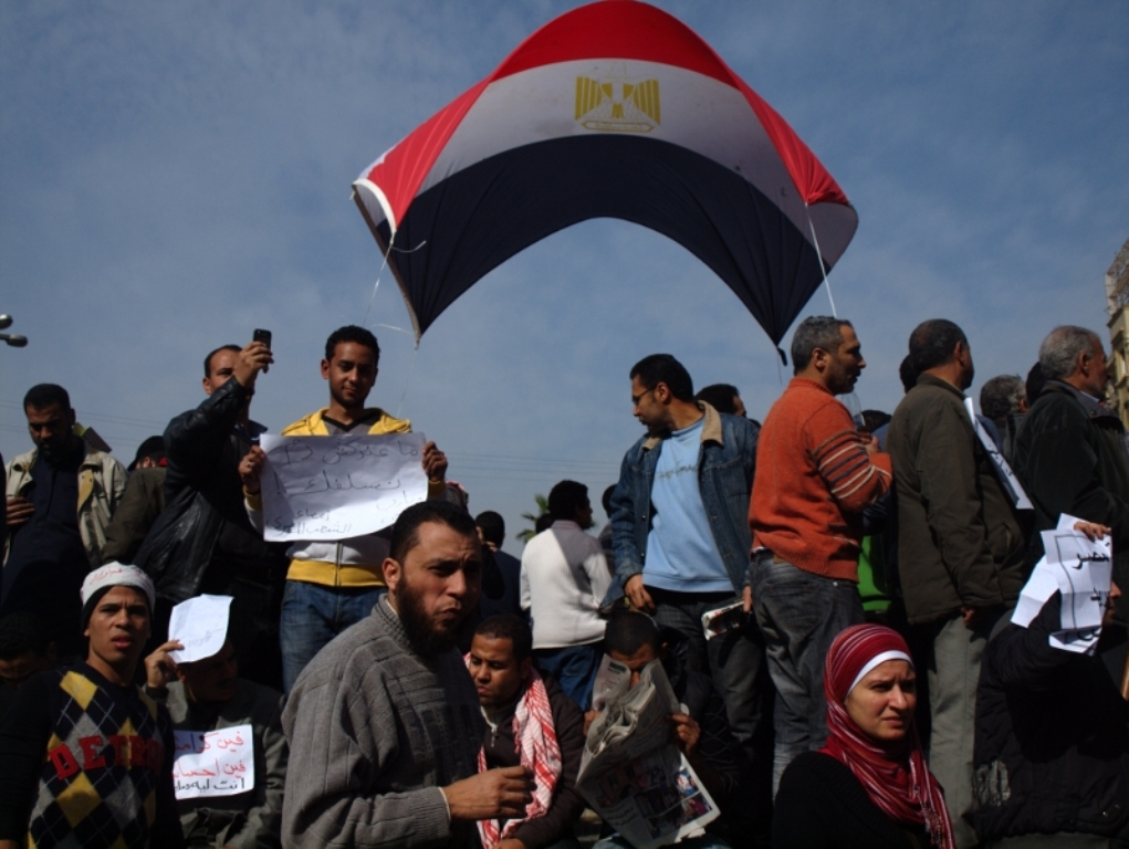 Egyptians raise their country's flag while they protest the leadership of Hosni Mubarak in Cairo's Tahrir Square in February 2011.