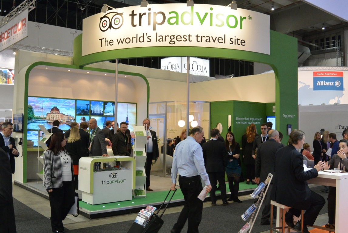 Convention goers explore a TripAdvisor booth.