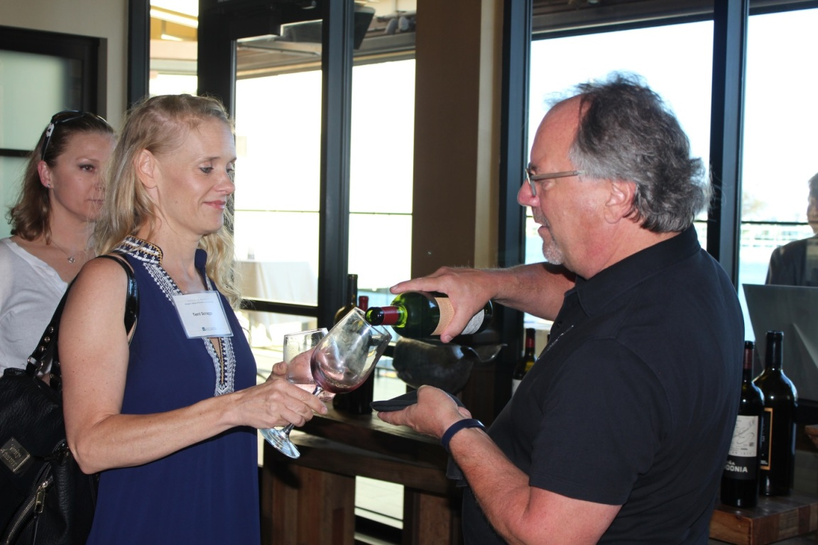 A middle-aged man pours a glass of wine for a middle-aged woman, both supporters of Cal State Fullerton's Mihaylo College, at the annual Summer Wine Mixer in 2016.