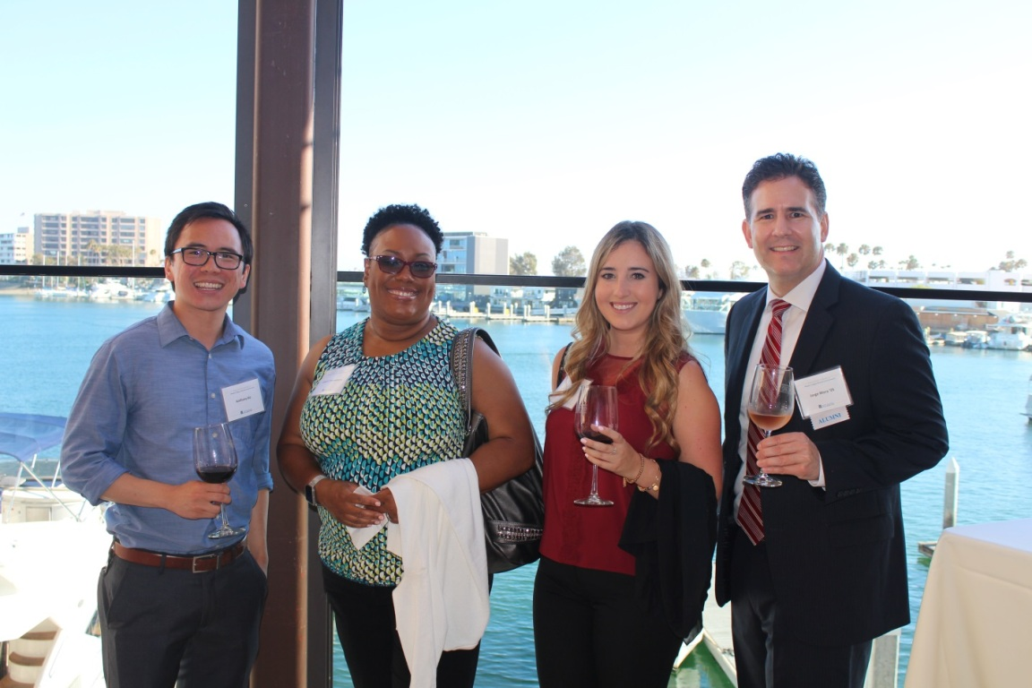 A group of four Mihaylo College Executive Council members stand with wine glasses in hand at the 2016 Summer Wine Mixer, with Newport Harbor in the background.