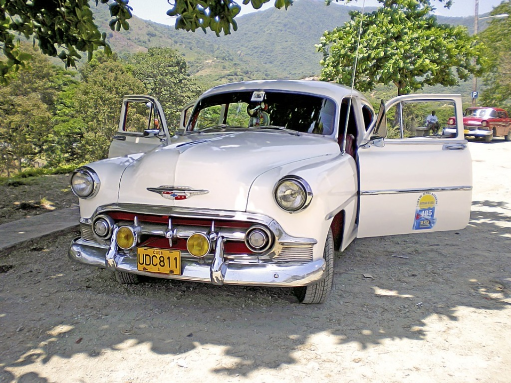 An antique car parked on the roadside in the mountains of Cuba.