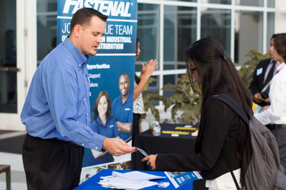 A Mihaylo College student receives materials from a representative of Fastenal at a career fair sponsored by the Sales Leadership Center.