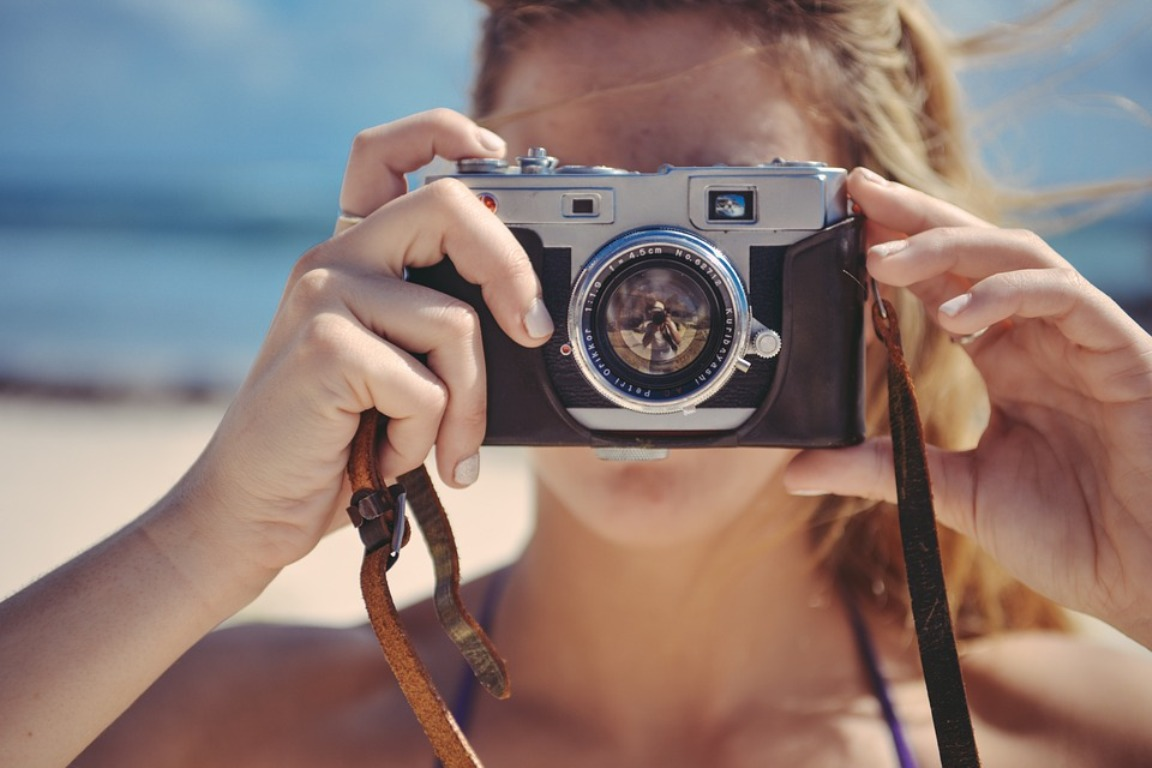 A young woman pointing a digital camera at the viewer, with a beach in the background.