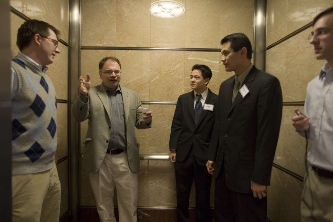An entrepreneur gives an all-important 60-second pitch to several businessmen while riding an elevator in an office building.