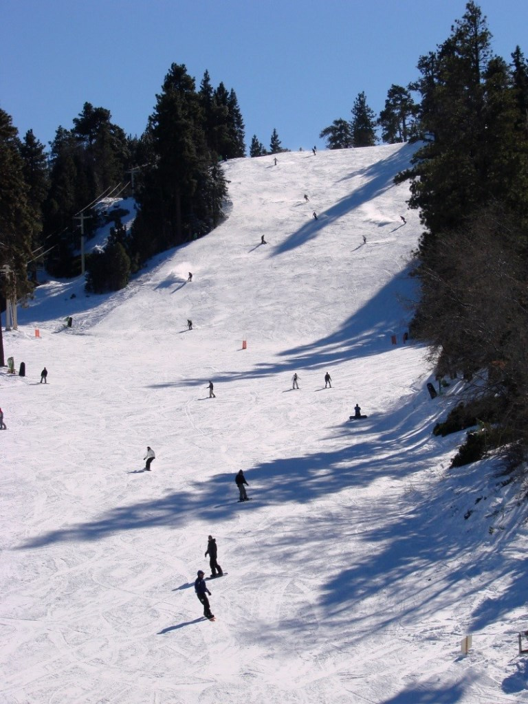 Skiers and snowboards descend the slopes on a sunny winter day at Snow Summit near Big Bear Lake, California.