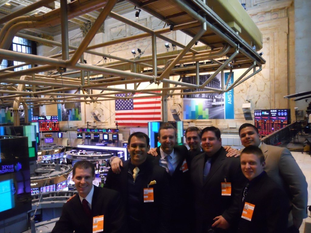 Seven Mihaylo College ASAP students pose at the New York Stock Exchange on Wall Street.