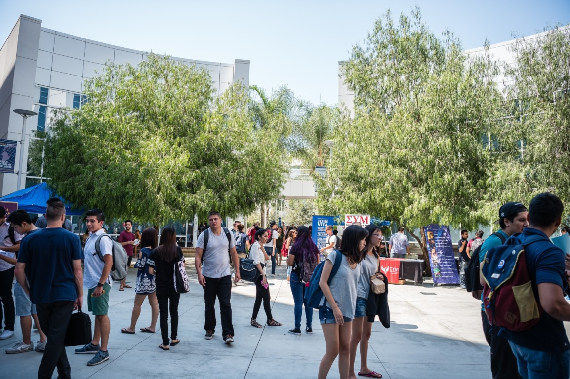 Mihaylo College students walk amidst tables with representatives from student clubs in the courtyard of Steven G. Mihaylo Hall at Cal State Fullerton.