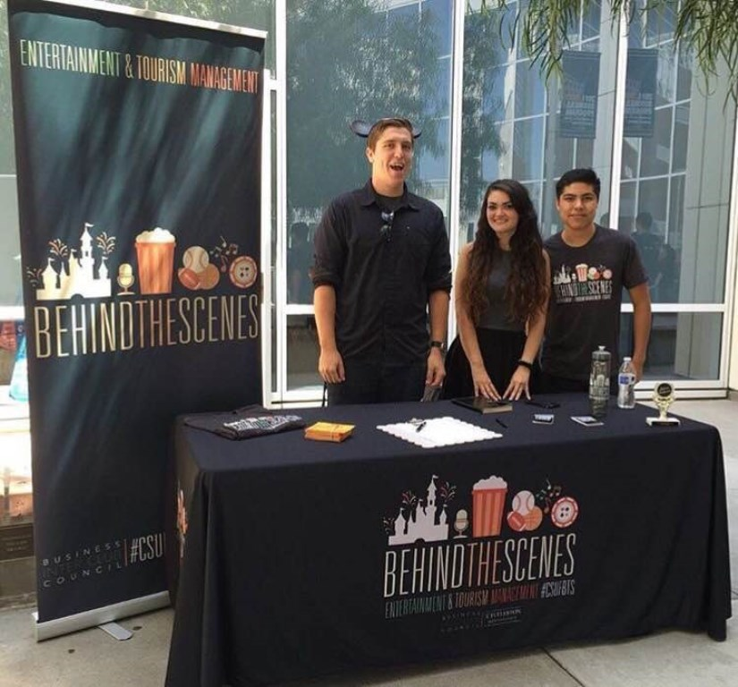 Three students at a table representing the Behind the Scenes club at an event in the courtyard of Steven G. Mihaylo Hall at Cal State Fullerton.