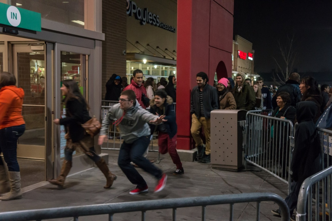 A large and diverse group of shoppers rush through barricades into a store in an outdoor strip mall on Black Friday.
