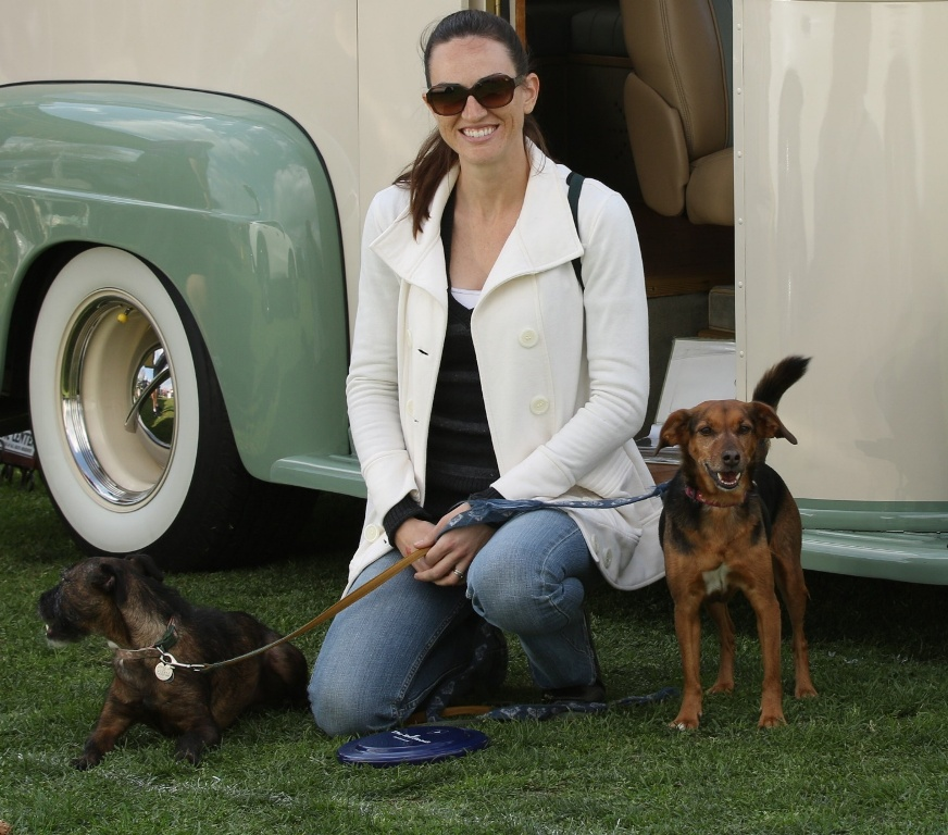Mihaylo College grad Erin Foate '07, founder of Dachs 2 Danes, a pet care startup, kneels, holding dogs on either side.