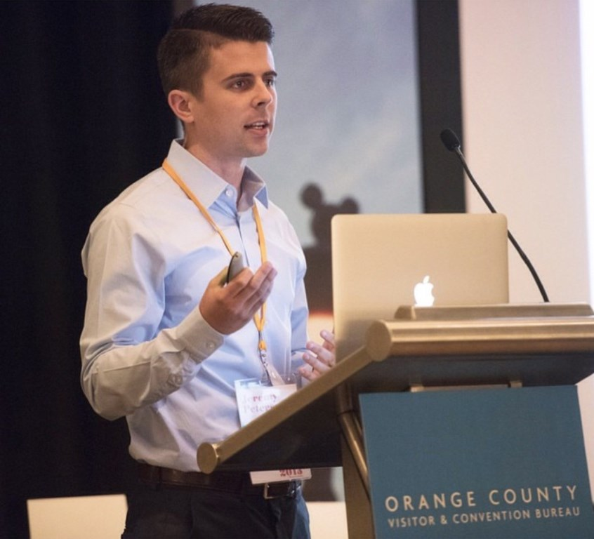 Mihaylo College grad Jeremy Peterson '14 standing behind a podium representing the Orange County Convention and Visitors Bureau at a conference in Canada.