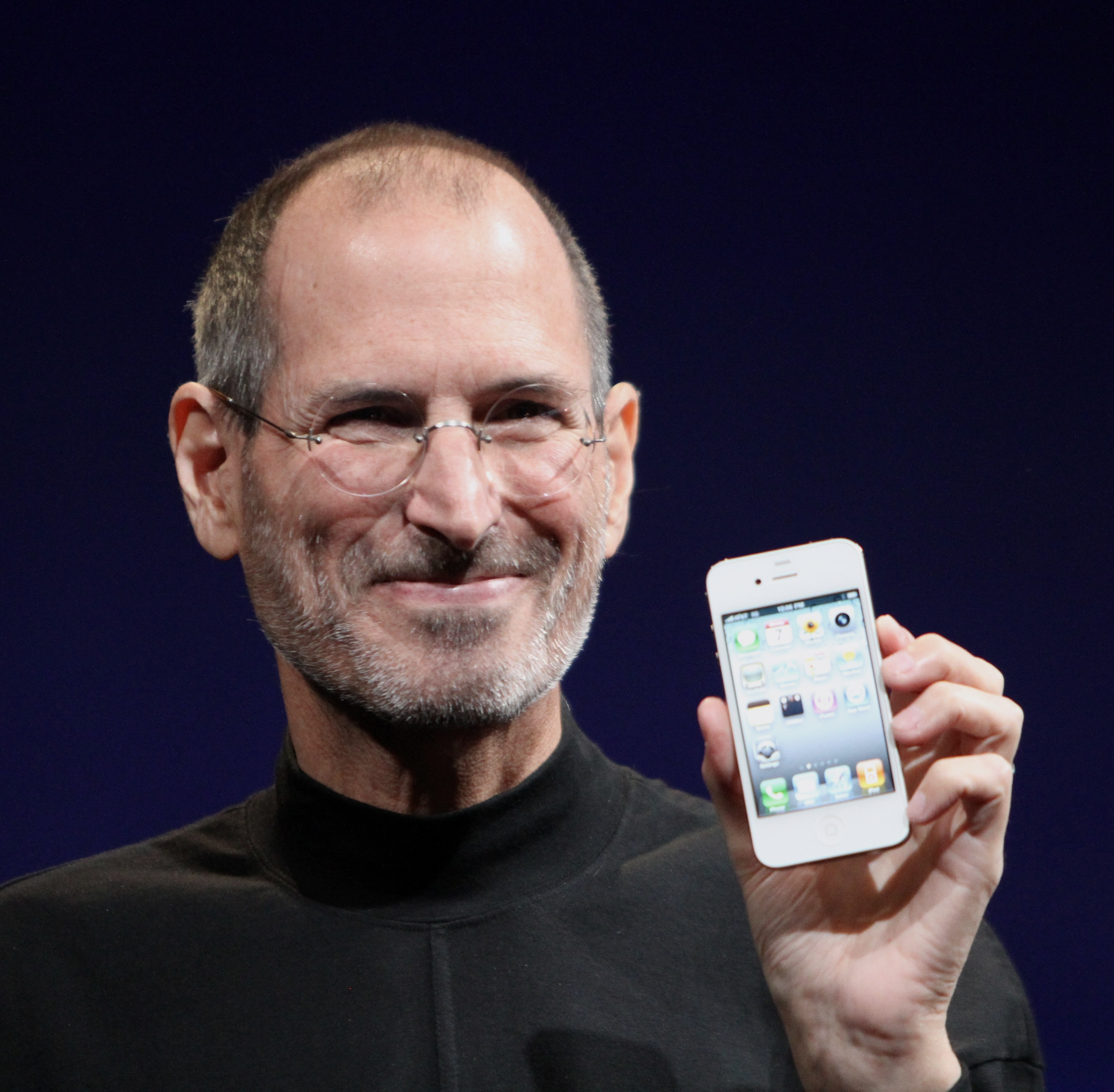 Steve Jobs, the late founder and CEO of Apple Inc., holds an iPhone.