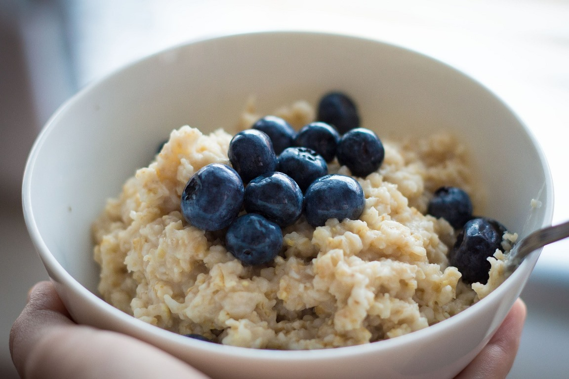 A person holds a cup of oatmeal topped with blueberries, a combination believed to provide extra brain power for test-takers.