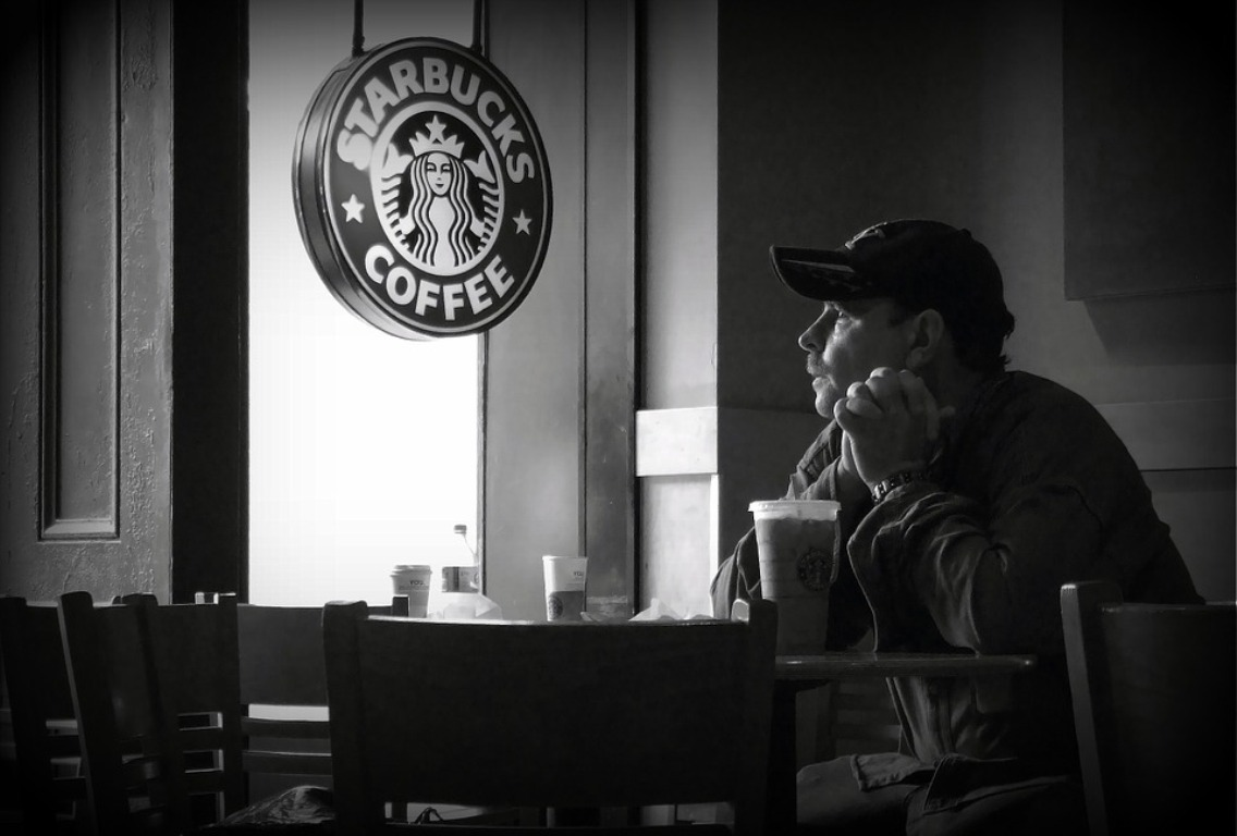 A man seated at a table at a Starbucks looks out the window.