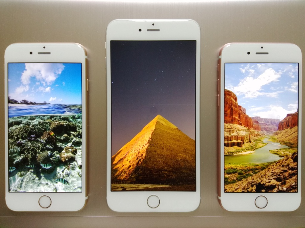 Three iPhones with screens displaying major world landmarks, including the pyramids, a Southwest canyon and undersea treasures.