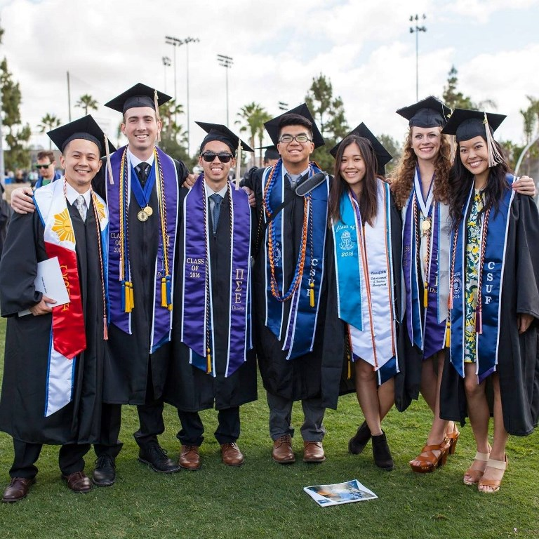 Graduating CSUF Pi Sigma Epsilon students pose in cap and gown at the 2016 commencement.
